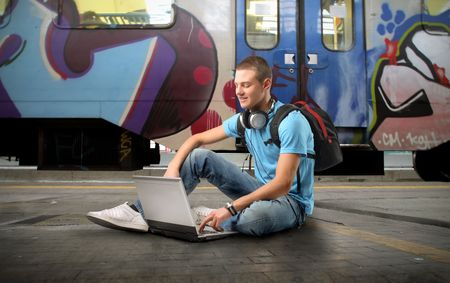work station: Young man sitting on a platform of a train station and using a laptop