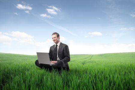 Geschäftsmann auf einer grünen Wiese sitzen und einen Laptop verwenden