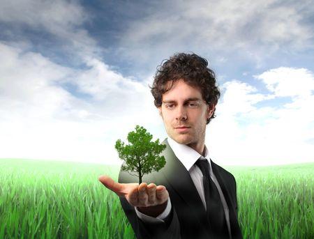 respeto: Empresario sosteniendo un �rbol en su mano