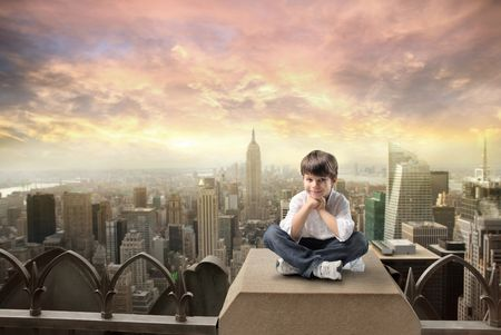 Smiling child sitting on the rooftop of a skyscraper with cityscape on the background Stock Photo