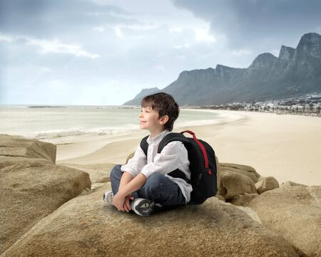 Smiling child with rucksack sitting on a rock at the seaside Stock Photo - 7225833