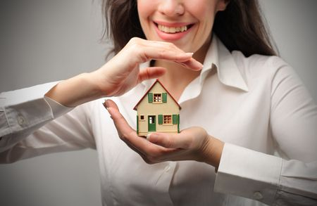 mortage: Smiling woman holding the model of a house