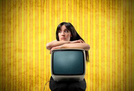 old technology: Donna infastidita con un vecchio rotto televisione sulle sue ginocchia