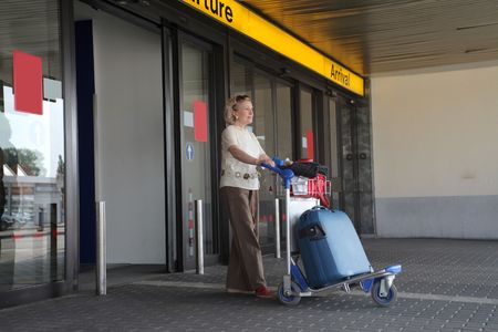 luggage airport: Senior woman coming out from an airport with luggage