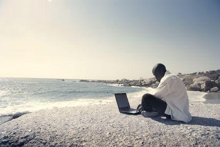 africa sunset: Uomo nero seduto su una spiaggia e utilizzando un computer portatile