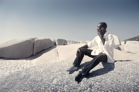 Black man sitting on the sand and talking to mobile phone photo