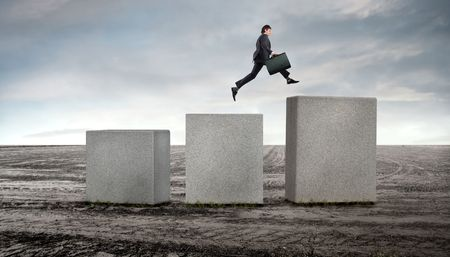 across: Businessman jumping from a cube to a higher one on a field