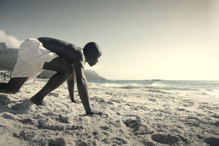 africa people: Young black man starting to run on a beach Stock Photo