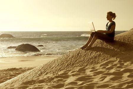 schreiben: Frau sitzt auf einem Strand und benutze ein laptop