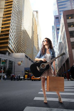 city street: Young woman carrying a shopping bag and a guitar standing on a city street Stock Photo
