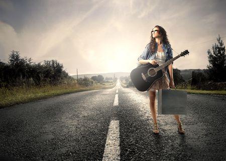 femme avec guitare: Jeune femme transportant un sac et une guitare debout sur une route de campagne  Banque d'images