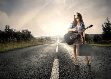 Young woman carrying a shopping bag and a guitar standing on a countryside road photo