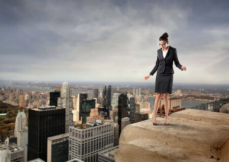 fear of failure: Businesswoman standing on the edge of a rooftop over a city Stock Photo