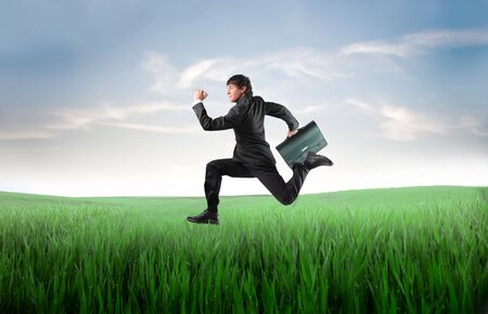 Businessman running on a green meadow Stock Photo - 7792014