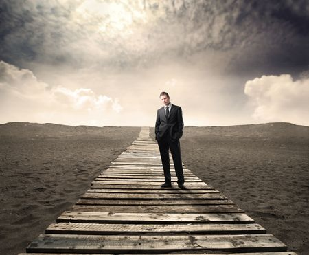Businessman standing on a wooden path in a desert photo
