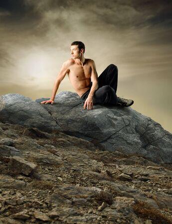assis par terre: Jeune bel homme torse nu assis sur un rocher