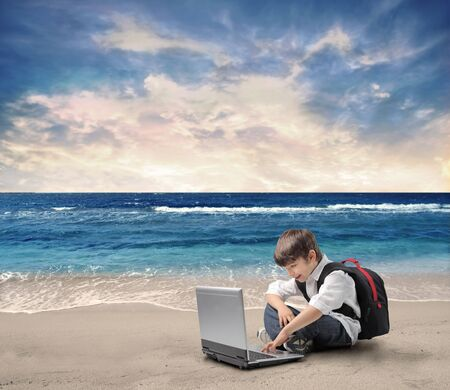 Smiling child sitting on a beach and using a laptop photo