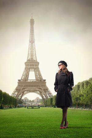 Elegante Frau stand in einem Park mit Eiffelturm auf dem Hintergrund