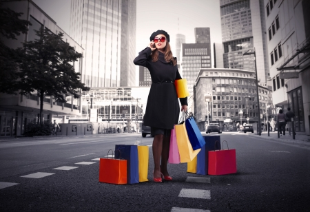 Elegant woman carrying some shopping bags and talking to telephone in a city street Stock Photo