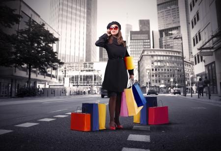 taxi: Elegante mujer llevando algunas bolsas de compra y hablando por tel�fono en una ciudad calle