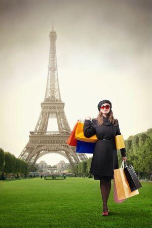 Elegante Frau trägt einige Einkaufstaschen mit Eiffelturm auf dem Hintergrund  Standard-Bild