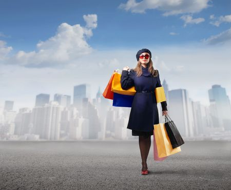 chicas comprando: Mujer elegante llevando algunas bolsas de compra con el paisaje urbano en el fondo