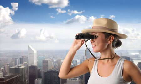 city trip: Smiling woman using binoculars with cityscape on the background Stock Photo