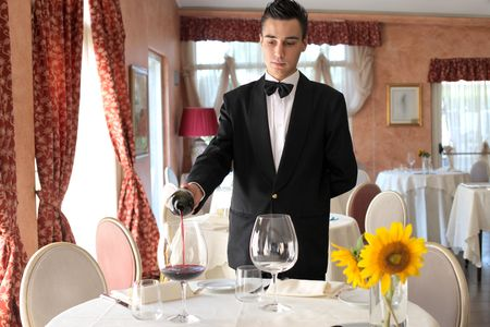 mesero: Joven camarero servir vino en un restaurante de lujo