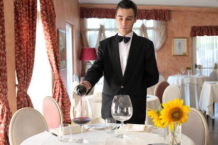číšník: Young waiter serving some wine in a luxury restaurant