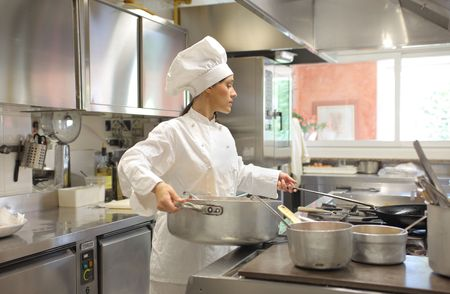 Female cook holding a pot in a restaurant kitchen photo