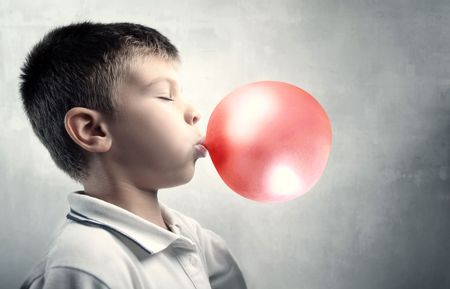 Child making bubbles with a chewing-gum photo