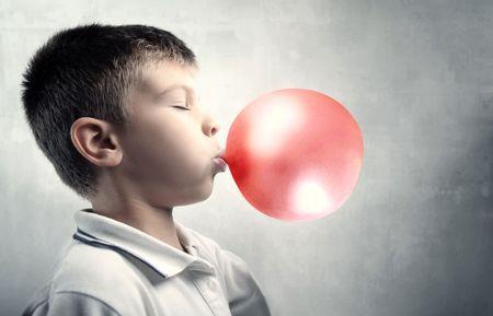 goma de mascar: Ni�o haciendo burbujas con una goma de mascar