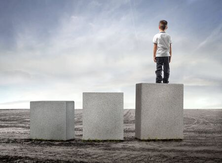 Child standing on the highest of three cubes in a field Stock Photo