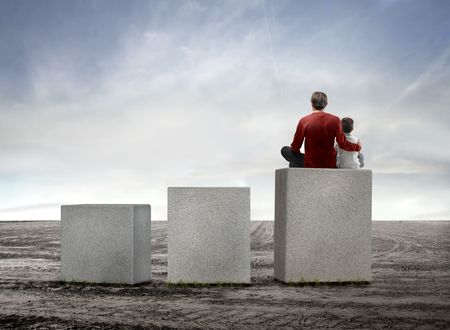 ascend: Father and son sitting on the highest of three cubes