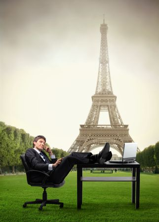 city trip: Businessman sitting at his desk and talking to telephone with Eiffel Tower on the background Stock Photo