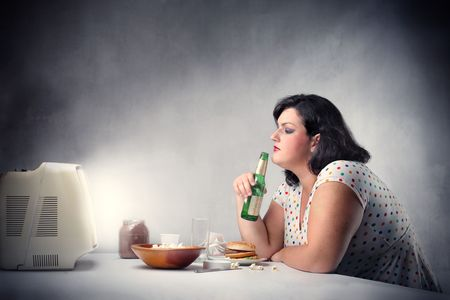 Fat woman drinking a beer in front of the television photo