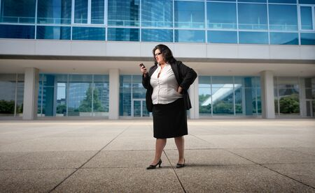 obese girl: Businesswoman using a mobile phone in front of an office building Stock Photo