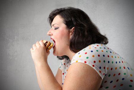 grasse: Femme en mati�res grasses, manger un hamburger  Banque d'images
