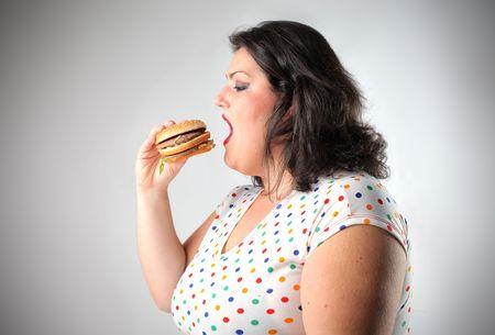 mujer gorda: Mujer grasa comer una hamburguesa