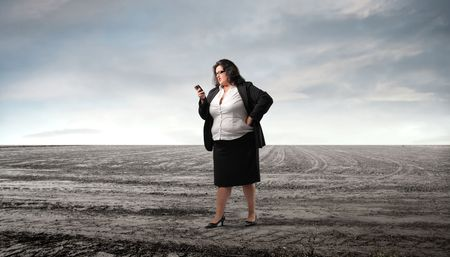 Businesswoman using a mobile telephone on a field photo