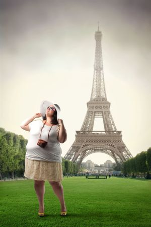 Fat tourist standing in a park with Eiffel Tower on the background photo