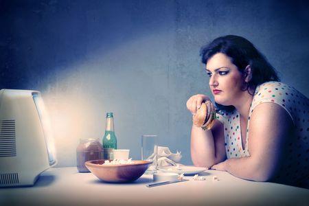 mujer gorda: Grasa mujer sosteniendo una hamburguesa al estar sentado en frente de la televisi�n  Foto de archivo