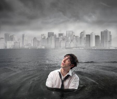 ahogarse: Empresario h�medo en el agua con cielo tormentoso por encima de �l  Foto de archivo