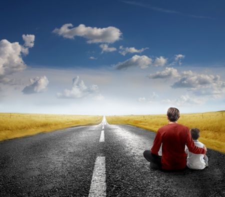Father and son sitting on a countriside road photo