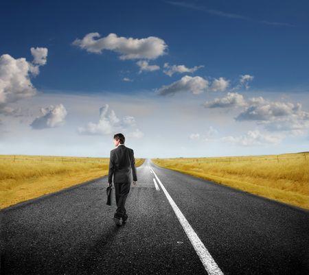 hombre solo: Empresario caminando por una carretera de campo