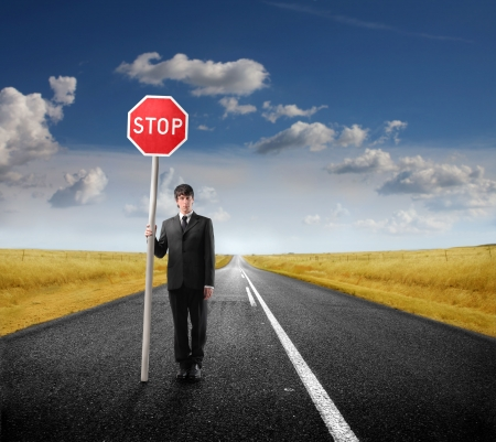 with stop sign: Businessman standing on a countryside road and holding a roadsign