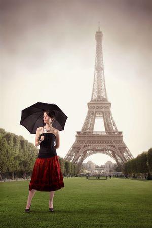 Beautiful Woman holding einen Regenschirm mit Eiffelturm auf dem Hintergrund