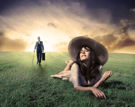 Smiling beautiful woman lying on a green meadow and gentleman approaching photo