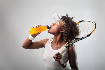 Joven negra en traje de tenis tomar una bebida de energía