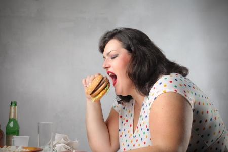 mujer gorda: Mujer grasa comer comida basura para la cena  Foto de archivo